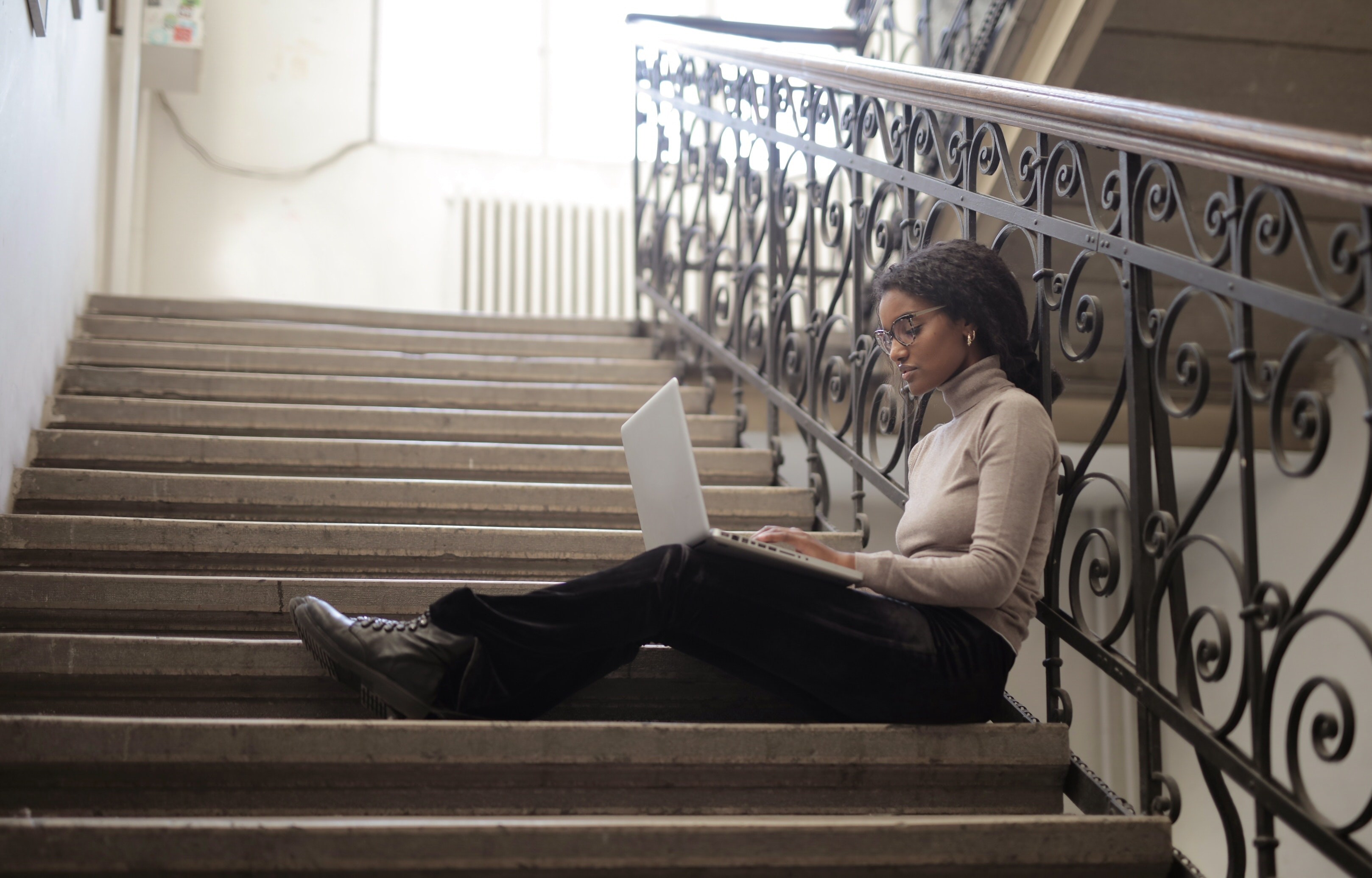 woman-sitting-on-staircase-while-using-her-laptop-3876811